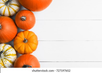 Many orange pumpkins on white wooden background, Halloween concept