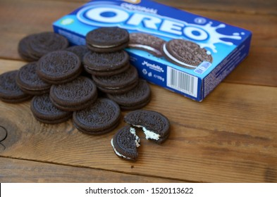 Many OREO sandwich cream biscuits with pack on wooden background