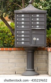 many organized mail boxes on stand pole