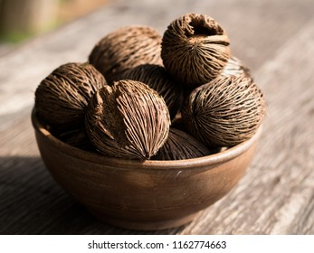 many oval coconut spathe in earthen bowl on wooden table