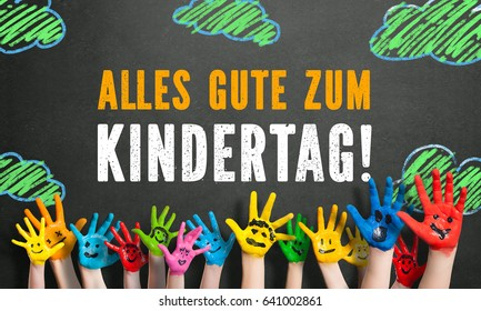 "many painted kids hands with smileys and the message ""Happy Children's Day"" (in German) on a blackboard"