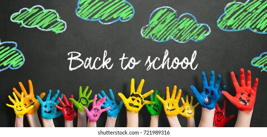 "many painted kids hands with smileys and the message ""back to school!"" on a blackboard"