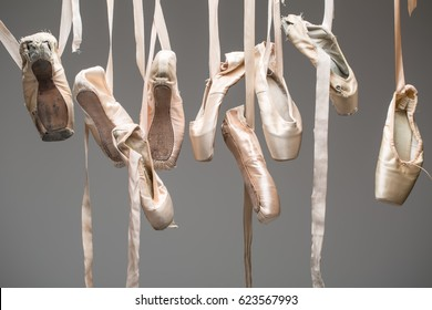 Many pairs of ballet shoes hang haphazardly on a hanger. Pointe in different condition from new to very shabby old. Horizontal.