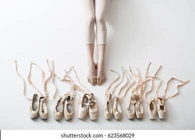 Many pairs of ballet shoes in pairs stand in a row. Legs of a young ballerina with bare feet. The girl's fingers are all covered in wounds and plasters. Pointe shoes in different condition from new to