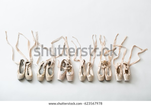 Many pairs of ballet shoes in pairs stand in a row. Pointe shoes in different condition from new to very shabby old. Tapes are accurately laid out in different directions. Studio shooting, horizontal