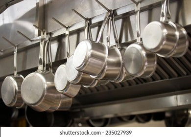 Many pans hanging in a restaurant kitchen