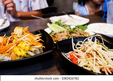 Many papaya salad and fruit salad are Thai food on the table in the restuarant.