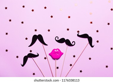 Many paper mustaches and red plastic lips on stick on pink background with stars and confetti. Bright and festive picture, masquerade and November concept. Top view, flat lay.
