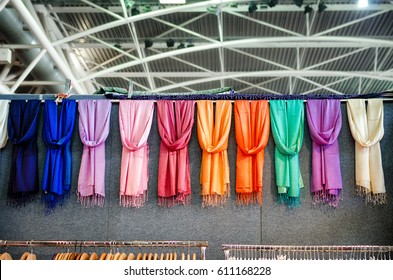 many pashmina foulards hanging from a market stall