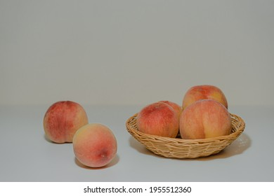 Many peaches are placed in a wicker basket on a clean, flat white table. There is a fresh blend of orange, yellow, and red color. Blurred picture of peach on the ground at left. - Shutterstock ID 1955512360