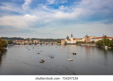 Many pedal boats in the Vltava River in Prague, with the Charles Bridge in the background