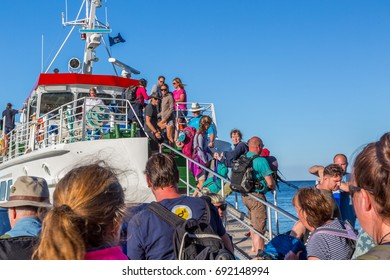 Many people entering a ship. Gotska sandon, Sweden - August 2, 2017: Ground view of crowd of people using a gangway to board a ship to leave the national park island Gotska sandon in the Baltic sea.