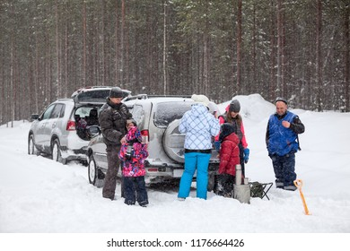 Many people family stops vehicles on winter road to rest, lunch time at blizzard and strong snowfall. Travel by car