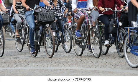 many people fast riding bicycles in Amsterdam in the Netherlands