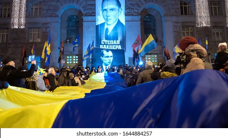 many people hold a very large Ukrainian national flag. Ukrainian nationalists torchlight procession (torch march) 111th anniversary of the birth of Stepan Bandera. January 1, 2020 Kyiv, Ukraine