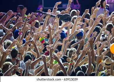 many people are  pointing their arms to the singer of the rockband