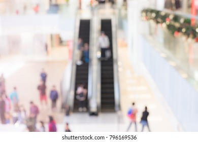 Many people in shopping mall and using escalator. blurred background concept.