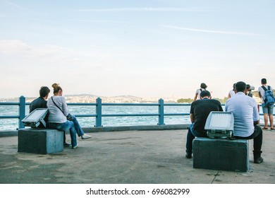 Many people sit on the observation platform under the Galata bridge and look at the view of the Bosphorus in Istanbul.