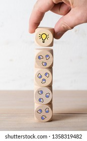 many people together having an idea symbolized by icons on cubes, stacked by a hand