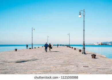 many people walking at famous Audace Pier in Trieste city, Italy