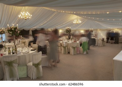 many people at a wedding reception in a marquee