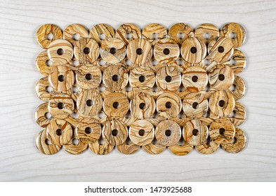 Many picture jasper stone donuts are laid in two layers on white wooden background