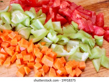 Many pieces of colored vegetables in rows, carrot, tomatoes and sweet pepper (paprika). Fresh chopped vegetables on a chopping wooden board. Chopped ingredients of salad. Sweet pepper and red carrot.