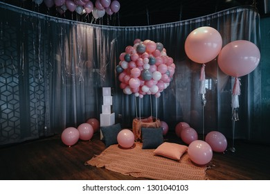 Many pink balloons and cushions with window screening in the lobby.