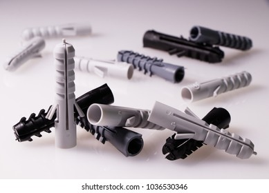 many plastic dowels on white background, wall plug - also known as screw anchor, construction tools