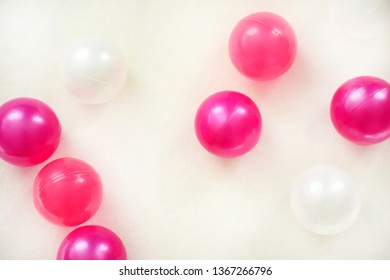 Many plastic pink and white balls on a white textile background. Children decoration concept.