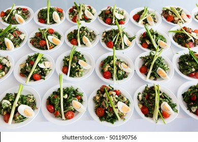 Many plates of vegetable salad in commercial kitchen