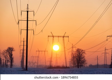 Many power lines with pylons and wires against rising sun