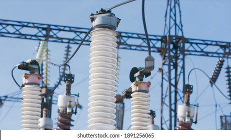 Many power poles in substation. Action. Electric substation with powerful equipment and transformers working in winter. Winter clear day at electric power station
