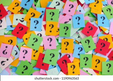 Too Many Questions. Big pile of colorful paper notes with question marks. Closeup.
