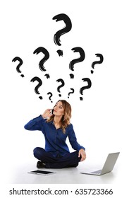So many questions! Confused woman, speaks by phone, sitting on the floor with a tablet and a laptop against a wall with question marks