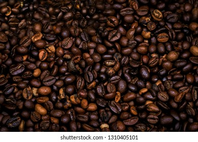 Many raw coffe beans. Texture coffe beans. Dark texture coffe beans. Photo for coffeshop. Picture for shop coffe.