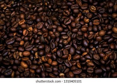 Many raw coffe beans. Texture coffe beans. Dark texture coffe beans. Photo for coffeshop. Picture for shop coffe.