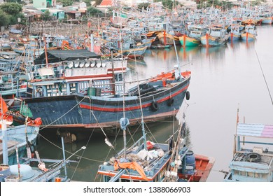 Many red and blue wooden boats smacks mooring in Binh Thuan, Vietnam