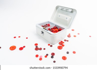 Many red buttons lie in an open petty cash and around