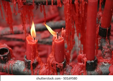 Many red candles with wax dripping in a Buddhist shrine in China.  Two of the candles have flames.