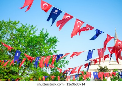 Many red flags of Turkey and blue flags of metropolitan municipalities decorate at Hippodrome square against of green leaves and blue sky. Turkish text means metropolitan municipalities.