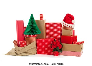 many red gifts for Christmas with hat of Santa, Poinsettia and tree  isolated over white background