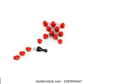 Many red meeple shaped like an arrow and one black meeple fallen out of line, white background and copy space