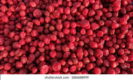 Many red plums dry the outdoors in a plum factory