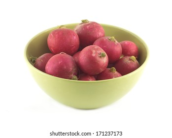 Many red radishes in green bowl closeup isolated on white