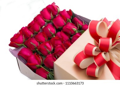 Many red roses arranged into a gift box on a white scene. As a gift in the festival
