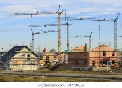 many residential houses under building construction with many cranes