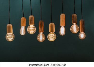 Many retro hanging lamps / blubs displayed in a showroom against dark green wall background.