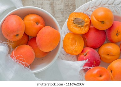 Many ripe apricots in a plate and a bowl. One apricot is opened.