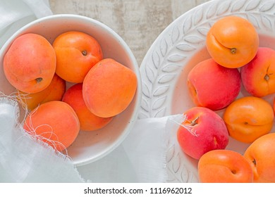 Many ripe apricots in a plate and a bowl.